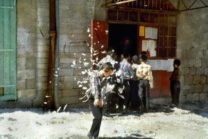 CHILDREN PLAYING WITH CHICKEN FEATHERS NEAR A BUTCHER SHOP, AT JERUSALEM'S MEA SHE'ARIM MARKET.ילדים משחקים בנוצות עופות ליד חנות למכירת בשר, בשוק במאה שערים בירושלים.