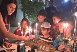 Audrey lighting hannukah candles with kids